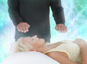 Female patient lying with eyes closed and male healer with hands hovering channeling energy with misty sparkling green energy field all around
