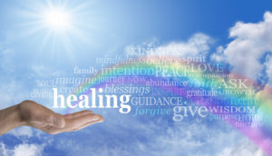 Blue sky and clouds with a man's hand palm up and the word 'healing' above as a rainbow arcs out of his palm with healing words floating across the rainbow