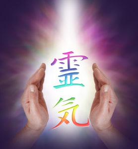Reiki Kanji Symbol floating between Male healer's hands with a shaft of white light behind on a dark background